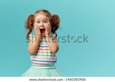 Portrait of surprised cute little toddler girl child standing isolated over blue background. Looking at camera. hands near open mouth #1460383406