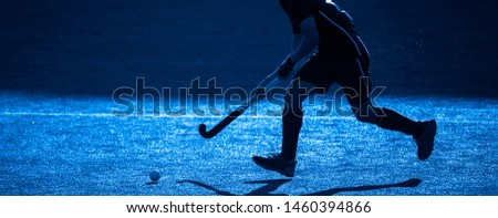 A Field Hockey Player About To Pass The Ball. Blue filter.