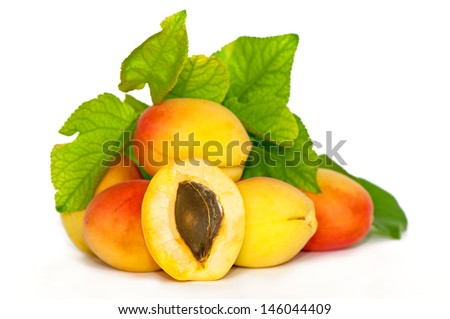 Apricots pile with leaves and bisected one in the center on a white background #146044409