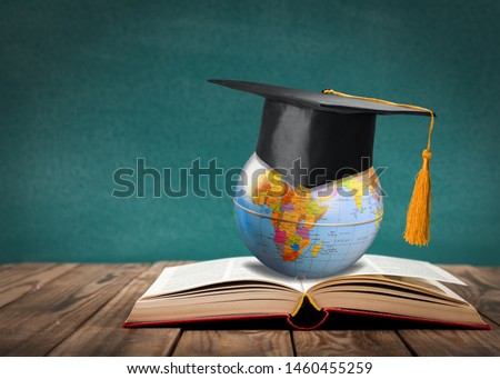 Education to learn study in world. Graduated student studying abroad international idea. Master degree hat on top globe book. Concept of graduate educational for long distane learning anywhere anytime #1460455259