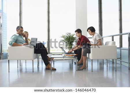 Full length side view of four business people sitting in modern waiting room at office #146046470