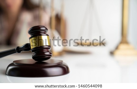Female lawyer, bokeh background, gavel, hourglass, scales, statue of justice.  #1460544098