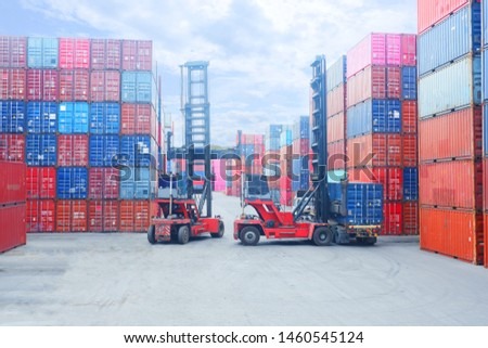 Forklift truck lifting cargo container in shipping yard or dock yard against sunrise sky with cargo container stack in background for transportation import,export and logistic industrial concept #1460545124