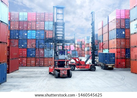 Forklift truck lifting cargo container in shipping yard or dock yard against sunrise sky with cargo container stack in background for transportation import,export and logistic industrial concept #1460545625