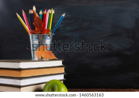 Colored pencils and fall leaves on stack of books. Green apple on wooden desk.  Classroom blackboard with copy space in background. Education, September, back to school concept #1460563163