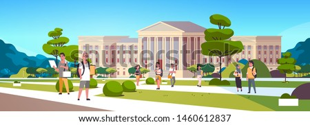 young mix race students group at campus yard education concept college friends relaxing and walking in front of university building exterior horizontal full length Royalty-Free Stock Photo #1460612837