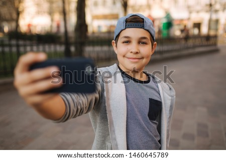 Young boy make a selfie on smartphone in the centre of the city. Cute boy in blue hat. Stylish school boy