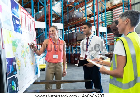Front view of diverse warehouse staffs discussing over whiteboard in warehouse. This is a freight transportation and distribution warehouse. Industrial and industrial workers concept #1460666207