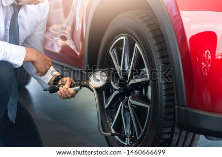 Asian man car inspection Measure quantity Inflated Rubber tires car.Close up hand holding machine Inflated pressure gauge for car tyre pressure measurement for automotive, automobile image #1460666699