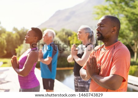 Four senior people meditating with joined hands and closed eyes breath deeply. Multiethnic class of mature people doing meditation with joined hands and relaxing together at park. #1460743829