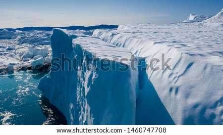 Flight over icebergs and shooting of ices at a short distance. An iceberg surface with thawing traces. Research of a phenomenon of global warming. Millions of tons of floating ice in the World Ocean #1460747708