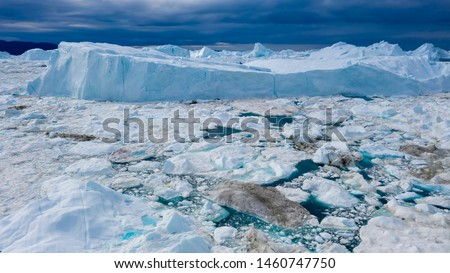 Flight over icebergs and shooting of ices at a short distance. An iceberg surface with thawing traces. Research of a phenomenon of global warming. Millions of tons of floating ice in the World Ocean #1460747750