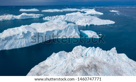Flight over icebergs and shooting of ices at a short distance. An iceberg surface with thawing traces. Research of a phenomenon of global warming. Millions of tons of floating ice in the World Ocean #1460747771