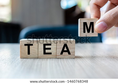 Businessman hand holding wooden cube block with TEAM business word on table background. Cooperation, Together, business and teamwork concept #1460768348