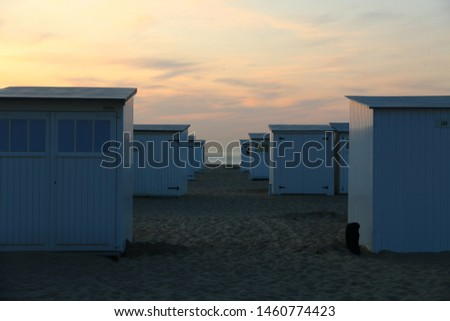 Typical white beach cabins along the Belgian coast are small wooden storage cabins, you rent for the season and use as a practical storage and changing room. These are pictured in Knokke Heist.