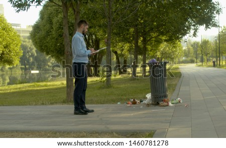 Inspector near the trash can and writing something in a notebook. #1460781278