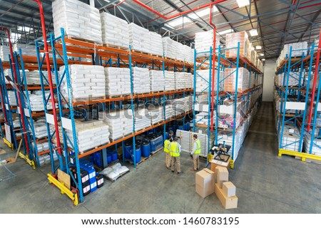 High angle view of mature diverse warehouse staff discussing over whiteboard in warehouse. This is a freight transportation and distribution warehouse. Industrial and industrial workers concept #1460783195