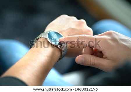 Man touching smart watch screen to open notification and read message. Wearable hybrid mobile device, gadget and activity tracker in wrist. Wearing digital smartwatch in hand. People with wearables. #1460812196