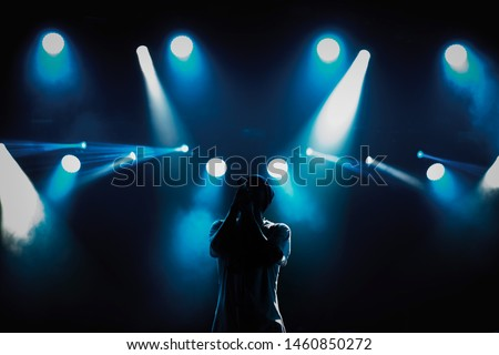 Cool young rap singer with microphone on bright backlit stage in bright blue lights.Hip hop star performing solo set on scene in music hall.Popular rapper sings a song on rock festival in nightclub #1460850272