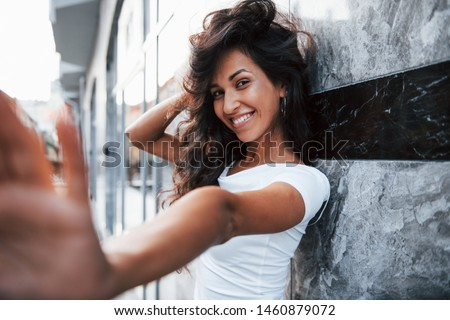 Positive girl. Beautiful woman with curly black hair have good time in the city at daytime. #1460879072