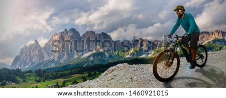 Man cycling on electric bike, rides mountain trail.  Man riding on bike in Dolomites mountains landscape. Cycling e-mtb enduro trail track. Outdoor sport activity. #1460921015