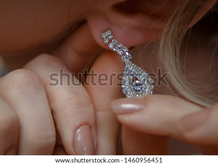 Wedding day. Wedding earrings on a female hand, she takes the earrings, the bride fees, morning bride, white dress, wear earrings. Earrings close-up in the hands of the bride. jewelry accessories #1460956451