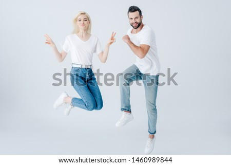 excited man and young woman jumping isolated on grey #1460989844