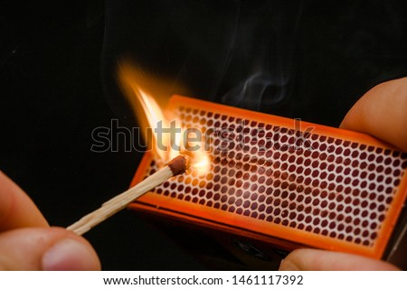 Man's fingers lighting a match, rubbing against the matchbox, setting fire to friction. On a black background. Matches and fire. #1461117392