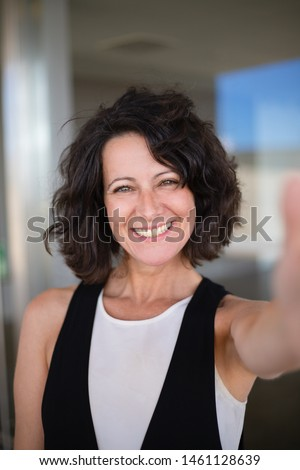 Selfie of happy joyful curly haired woman in casual. Excited middle aged lady holding smartphone and taking picture of herself. Happy woman portrait concept