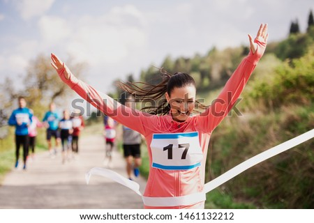 Young woman runner crossing finish line in a race competition in nature. #1461132212