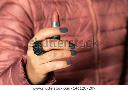 Close up of a real  woman hand holding red matte lipstick in red coat in the background. Painted nails and flower-shaped black wood ring on finger. Modern woman female power concept. #1461207209