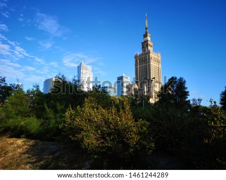 Warsaw, Poland - July 12, 2019: Palace of Culture and Science in Warsaw. Urban landscape, view of the city center behind green trees against the blue sky. #1461244289
