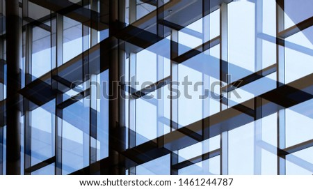 Glass wall with metal framework. Reworked photo of office building exterior or interior fragment with windows. Abstract modern architecture background with geometric structure with blue sky reflection Royalty-Free Stock Photo #1461244787