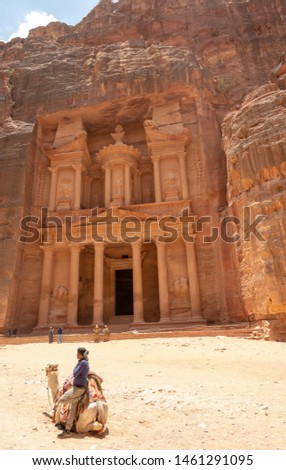 Petra, Jordan / June 17, 2019:  Originally known to its inhabitants as Raqmu. Petra was named among the New 7 Wonders of the World. Bedouin man on a camel. Tomb Stone. Cemetery. #1461291095