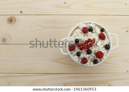Bowl with cottage cheese and fresh berries on wooden background  #1461360953