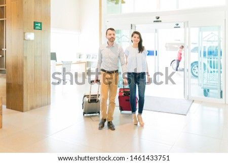 Full length of smiling mid adult couple pulling luggage while arriving at hotel on honeymoon Royalty-Free Stock Photo #1461433751