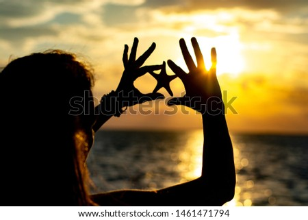 Girl near the sea at sunset with a starfish in the hands. Silhouette photo #1461471794