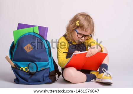 Children go back to school. Little happy girl doing homework at home with backpack full of books, pencils. Pupil reading a book, writing and painting. Kid is drawing. Child in glasses. #1461576047