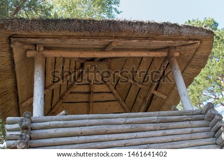 Vintage log timbered wooden watchtower with a thatched roof on the background of blue sky and overhanging trees. Bottom view. #1461641402