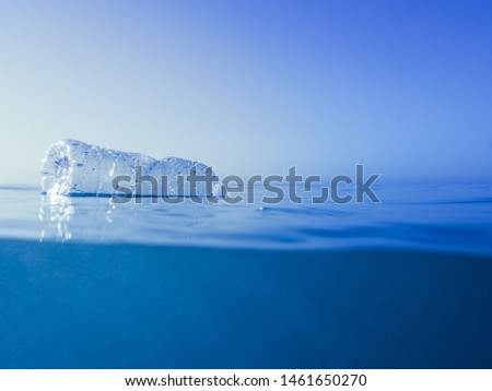 plastic waste at the ocean, a plastic bottle floating in the Mediterranean sea at the water surface, environmental problem with plastics pollution, copy space for text Royalty-Free Stock Photo #1461650270
