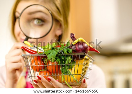 Woman using magnifying glass loupe, investigating shopping basket with many colorful vegetables. Healthy eating lifestyle, nutrients vegetarian food, searching for pesticides and chemicals. #1461669650