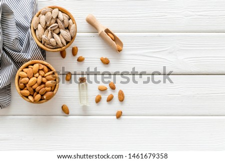Almond in bowls for cooking oil on white wooden background top view mockup #1461679358