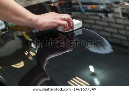 The process of applying a nano-ceramic coating on the car's hood by a male worker with a sponge and special chemical composition to protect the paint on the body from scratches, chips and damage. Royalty-Free Stock Photo #1461697349