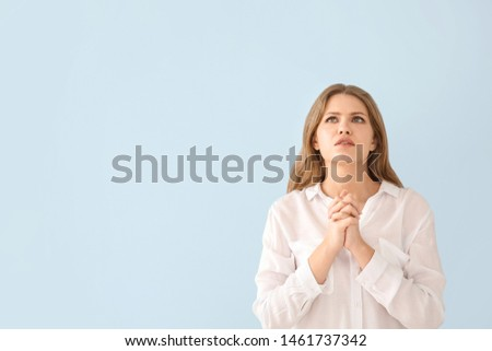 Religious young woman praying to God on light color background #1461737342