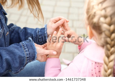 Mother teaching her deaf mute daughter to use sign language outdoors #1461737348