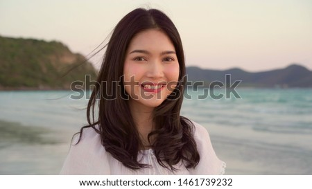Young Asian woman feeling happy on beach, beautiful female happy relax smiling fun on beach near sea when sunset in evening. Lifestyle women travel on beach concept. #1461739232