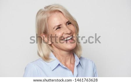 Cheerful senior businesswoman isolated on grey studio wall #1461763628