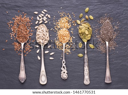 Various seeds - sesame, flax seed, sunflower seeds, pumpkin seed, chia in spoons on a black stone background. Top view #1461770531