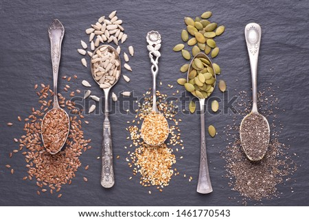 Various seeds - sesame, flax seed, sunflower seeds, pumpkin seed, chia in spoons on a black stone background. Top view #1461770543