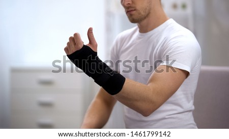 Male looking at hand with titan wrist support, orthopedic equipment, trauma #1461799142